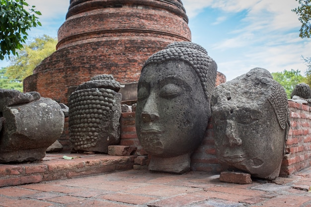A cabeça de uma imagem de buda de pedra em uma cerca velha no templo ratchaburana, província de ayutthaya, tailândia