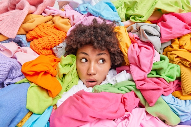 A cabeça de uma mulher projetando-se através de diferentes roupas multicoloridas desvia o olhar com expressão atordoada e arruma o armário para limpar as roupas desnecessárias do guarda-roupa mulher viciada em compras posa em torno de trajes