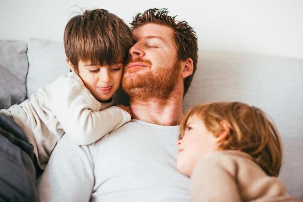 A cabeça do pai inclina-se contra o filho no sofá
