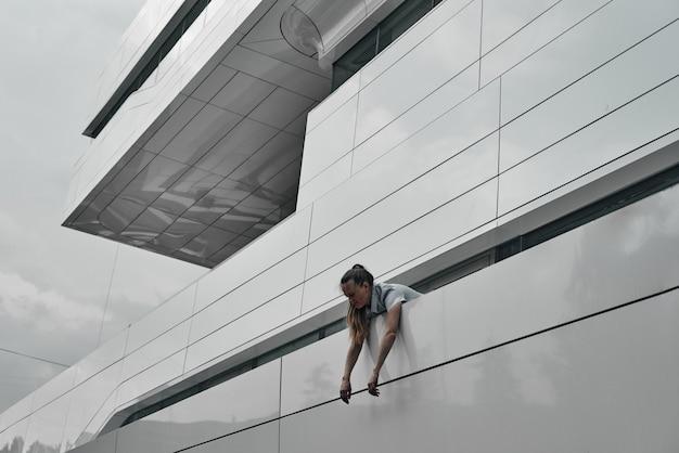 A cabeça e os ombros da garota estão contra o fundo do prédio, seus braços pendurados sobre a cerca. geometria em construção.