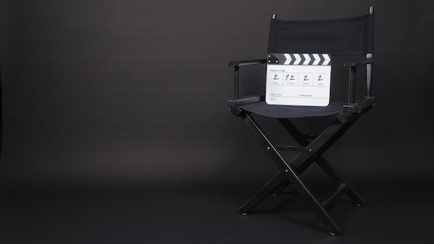 A cadeira do diretor e a claquete preta ou a tela de cinema usam na produção de vídeo e na indústria cinematográfica, cinematográfica e cinematográfica em fundo preto. está escrito em número.