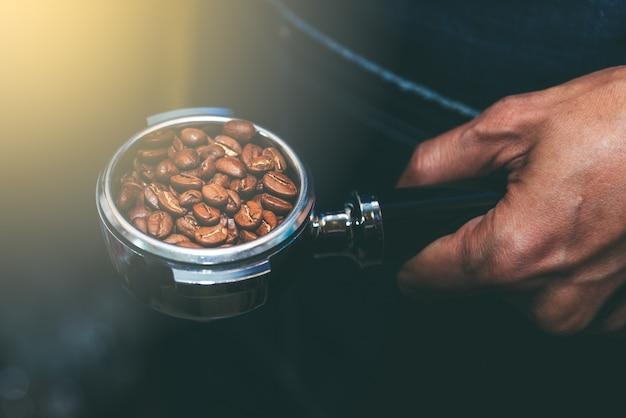 A cafeteira contém um dispositivo que contém grãos de café.