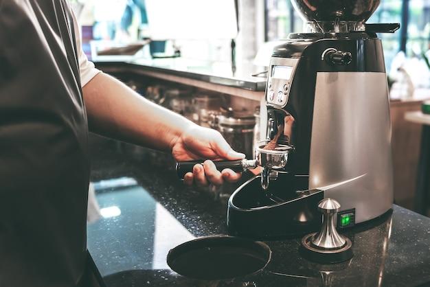 A cafeteira estava moendo os grãos de café em pó com um moedor de café automático