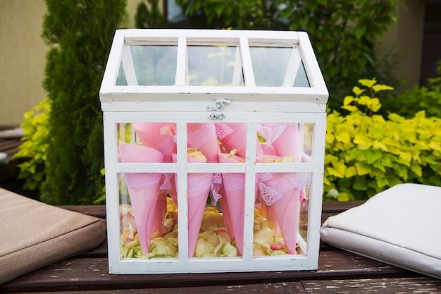 A caixa de madeira cheia de pétalas de rosa ao ar livre estilo antigo
