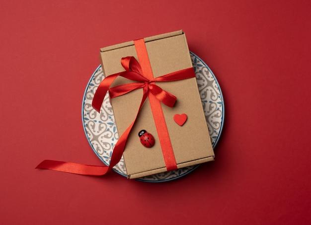A caixa de papelão marrom retangular amarrada com uma fita de seda vermelha encontra-se em uma placa redonda de cerâmica vermelha, vista de cima