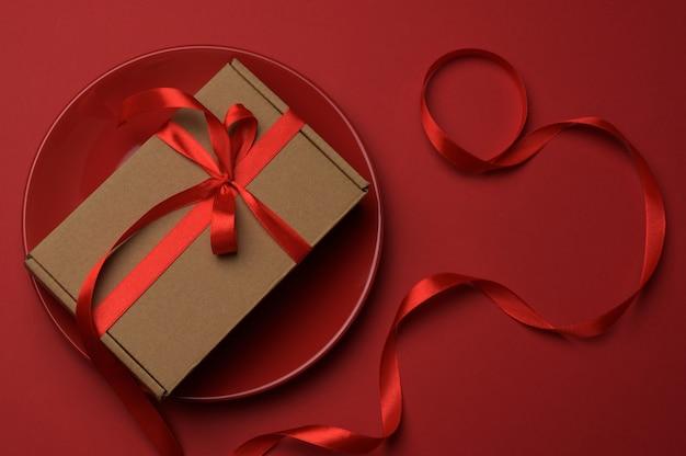 A caixa de papelão marrom retangular amarrada com uma fita de seda vermelha encontra-se em uma placa redonda de cerâmica vermelha