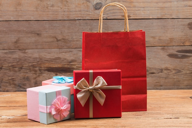 A caixa de presente amarrou uma fita vermelha com pequenos corações vermelhos impressos sobre ela. no fundo de madeira velha.