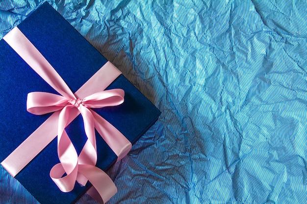 A caixa de presente azul escuro com decoração de fita rosa em papel azul de polca