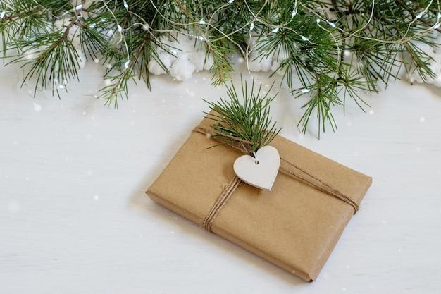 A caixa de presente de natal hnadmade embrulhada em papel artesanal marrom na mesa festiva.