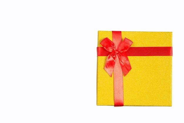A caixa de presente dourada é amarrada com uma fita vermelha com um laço em um fundo branco e isolada. copie o espaço. presente de natal, ano novo, aniversário, feriado.