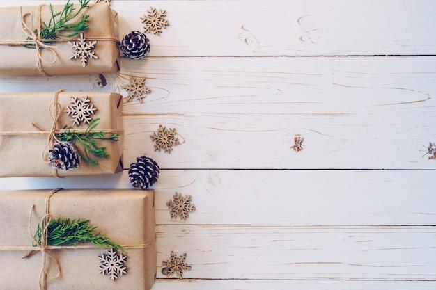 A caixa de presente envolvida caseiro do natal apresenta em um fundo de madeira da tabela com espaço.