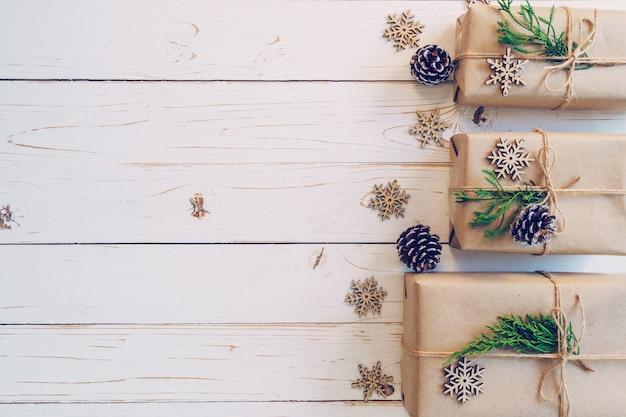 A caixa de presente envolvida caseiro do natal apresenta em um fundo de madeira da tabela.