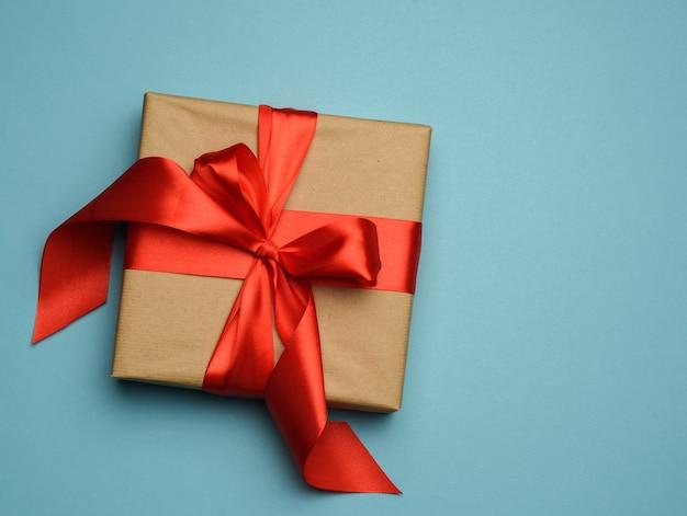 A caixa de presente quadrada é embalada em papel vermelho e fita de seda vermelha enrolada, fundo festivo, vista de cima