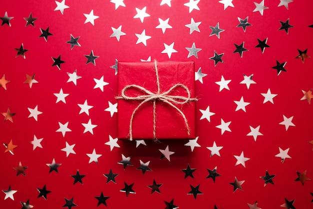 A caixa de presente vermelha do natal com estrela de prata polvilha no backgound vermelho. lay plana.