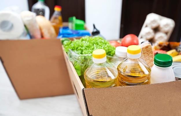 A caixa ecológica completa de papelão com produtos do supermercado no chão em casa perto da porta