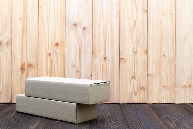 A caixa ou a bandeja de cartão vazia do marrom do pacote no fundo de madeira, zombam acima para o artigo longo.