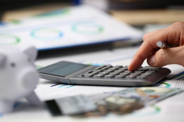 A calculadora de prata da tecla da mão masculina é