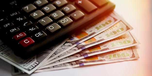 A calculadora preta fica de lado sobre os dólares espalhados como um leque