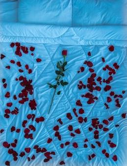 A cama com pétalas de rosa e uma flor. noite, noite, vista de cima