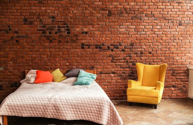A cama de casal moderna e a poltrona amarela estão contra o fundo da parede de tijolos. foto horizontal