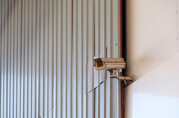 A câmera de vídeo de segurança suja está pendurada em uma posição alta perto da entrada do armazém no parque industrial, vista frontal para o fundo.