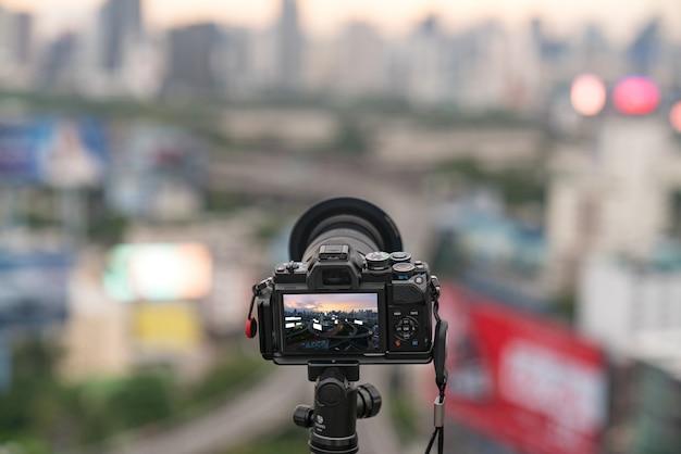 A câmera na cidade borrada de fundo