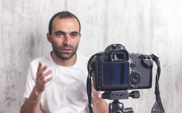 A câmera no tripé está filmando um homem. blogger