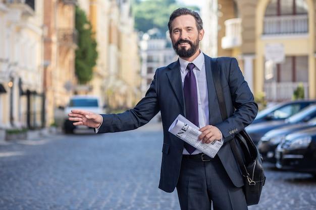 A caminho. homem de negócios profissional e alegre esperando por uma carona enquanto segura um jornal
