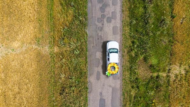 A caminhonete carrega um grande abacaxi inflável ao longo da estrada da vila entre os campos