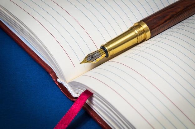 A caneta dourada fica em um caderno aberto para anotações ou texto escrito