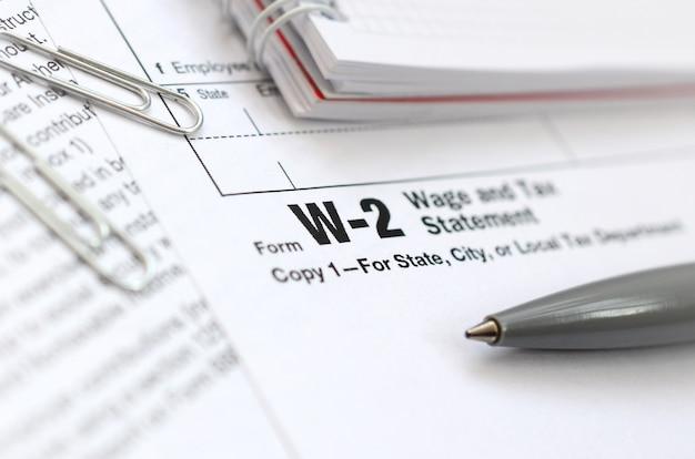 A caneta e o caderno no formulário de imposto w-2 wage and tax statement. o tempo para pagar impostos