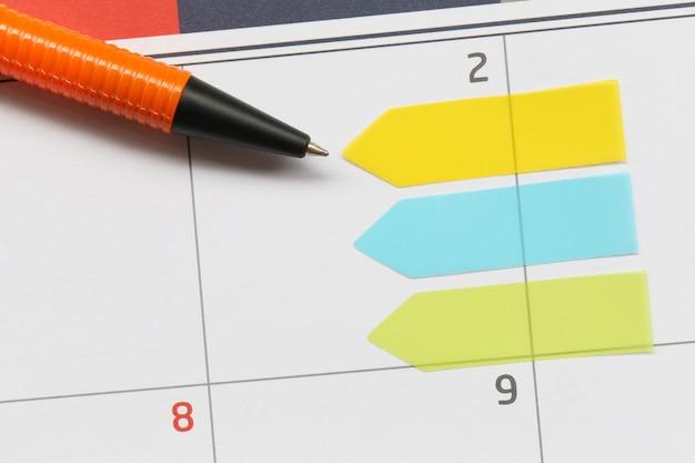 A caneta laranja aponta para uma área vazia no plano de fundo do calendário.