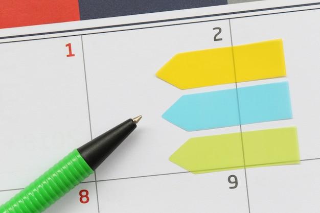 A caneta verde aponta para uma área vazia no plano de fundo do calendário.