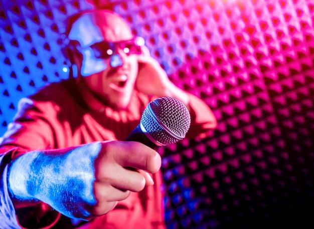 A cantora canta com um microfone no estúdio de gravação.