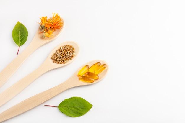 A cápsula erval, vitaminas naturais, calêndula seca floresce na colher de madeira no fundo branco. conceito de saúde e medicina alternativa: homeopatia e naturopatia.