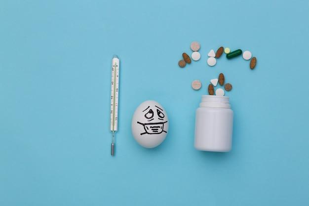 A cara do ovo em uma máscara médica, comprimidos e termômetro sobre fundo azul. pandemia do covid19. vista do topo