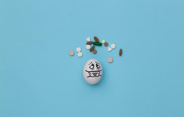 A cara do ovo em uma máscara médica e comprimidos sobre fundo azul. pandemia do covid19. vista do topo
