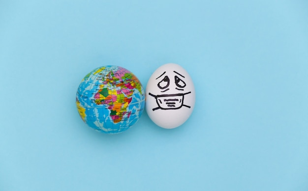 A cara do ovo em uma máscara médica e um globo sobre fundo azul. pandemia do covid19. vista do topo
