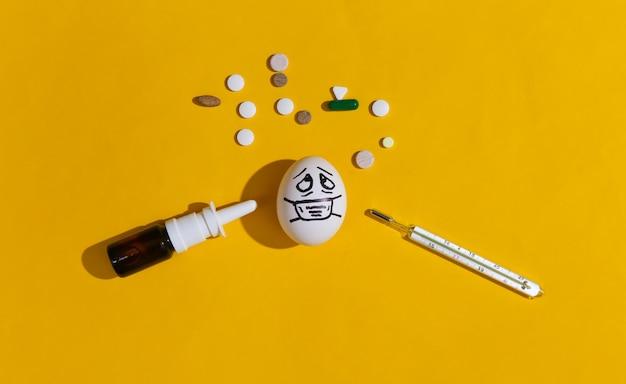 A cara do ovo em uma máscara médica, pílulas e termômetro em fundo amarelo brilhante. pandemia do covid19. vista do topo