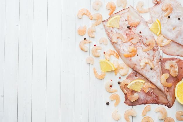 A carcaça crua do calamar e do camarão com especiarias e limão está pronta para cozinhar na tabela.