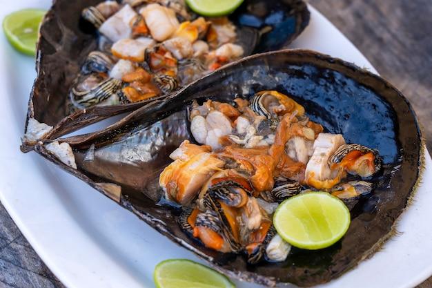 A carne crua de molusco em uma concha grande serviu de alimento em um restaurante local na ilha de zanzibar, tanzânia, áfrica oriental