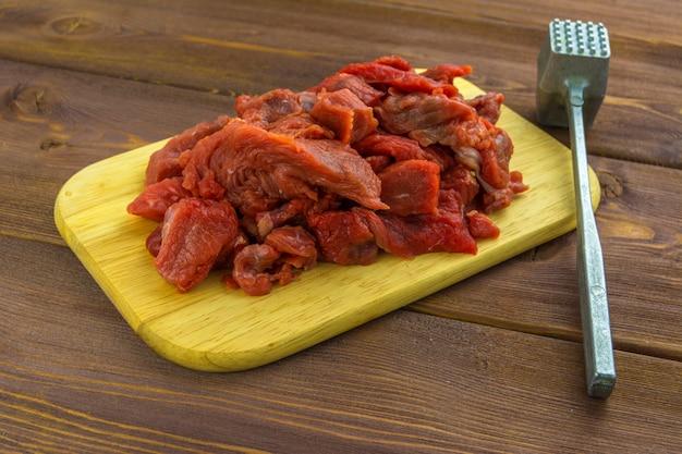 A carne da carne cortada em pedaços encontra-se em uma placa de madeira. martelo de metal para bater carne