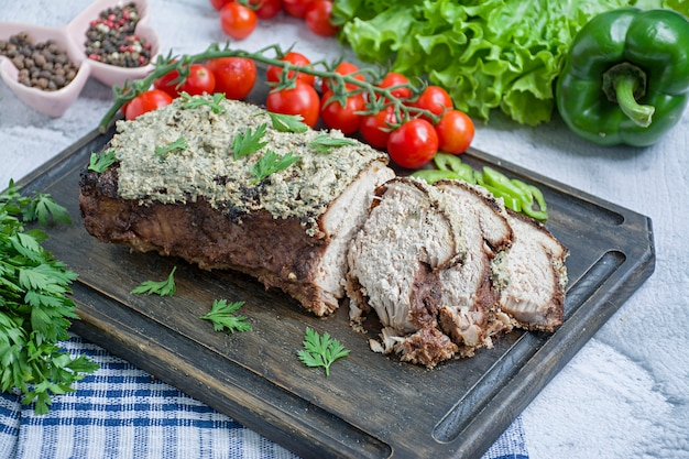 A carne de porco cozida desbastou em um molho da noz e de hortelã em uma placa de corte com ervas e os vegetais frescos.