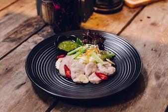 A carne de porco cozinhando tailandesa serviu com molho picante.