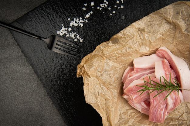 A carne de porco é empilhada no papel e um garfo e pimenteiro também são colocados