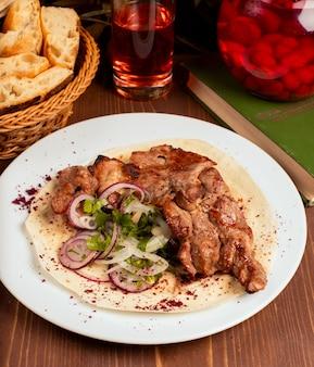 A carne, no espeto do cordeiro serviu com fatias da cebola, vegetais e ervas, lavash na placa branca.