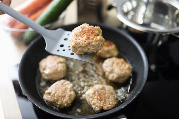 A carne picada em forma de costeleta é frita na frigideira