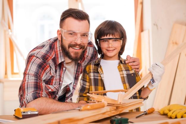 A carpintaria é uma empresa familiar. jovem carpinteiro alegre abraçando seu filho enquanto se inclina na mesa de madeira com diversas ferramentas de trabalho colocadas sobre ela
