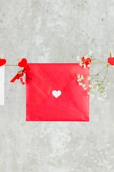 A carta de amor paira sobre uma corda e uma flor sobre um fundo claro.