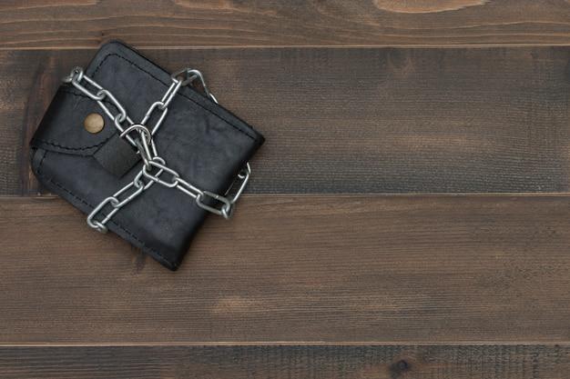 A carteira de couro com o cacifo chain na tabela de madeira, dinheiro protege o conceito.